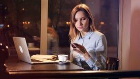 Café de consumición de la mujer joven cerca de la ventana del panoramiv Computadora portátil en el vector metrajes