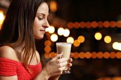 Café de consumición de la mujer joven en un café Foto de archivo