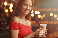Café de consumición de la mujer joven en un café Foto de archivo libre de regalías