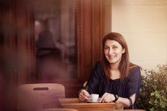 Café de consumición de la mujer joven en un café al aire libre Tono de Brown Fotografía de archivo libre de regalías