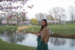 Café de consumición de la mujer joven de una taza de papel que lleva la falda esmeralda del color - flor de cerezo colorida de Sa imágenes de archivo libres de regalías