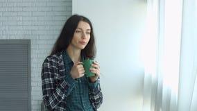 Café de consumición de la mujer linda y mirada hacia fuera de la ventana metrajes