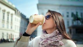 Café de consumición de la mujer de la moda a ir de la taza de papel que disfruta de la rotura en el paisaje urbano al aire libr almacen de metraje de vídeo