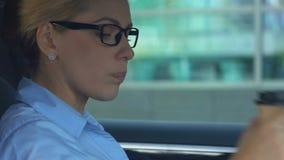 Café de consumición de la mujer de negocios durante el automóvil que conduce, energía de la mañana almacen de metraje de vídeo