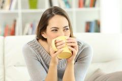 Café de consumición de la mujer que mira el lado en casa Fotos de archivo