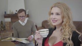 Café de consumición de la mujer rubia hermosa en el primero plano mientras que hombre modesto vestido que lee el libro en el fond almacen de video