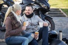 Café de consumición de los pares cerca de la motocicleta Fotos de archivo libres de regalías