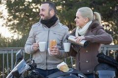 Café de consumición de los pares cerca de la motocicleta Foto de archivo libre de regalías