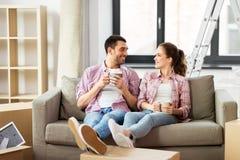 Café de consumición de los pares felices que se mueve al nuevo hogar foto de archivo libre de regalías