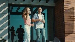 Café de consumición de los pares hermosos en terraza Exterior que habla del hombre y de la mujer almacen de video