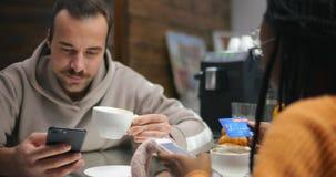 Café de consumición de los pares Muchacha del Afro que paga en línea mercancías usando tarjeta de crédito almacen de metraje de vídeo