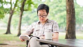 Café de consumición mayor asiático del libro de lectura de la mujer en el parque soleado, g Imágenes de archivo libres de regalías
