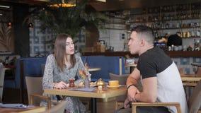 Café de consumición mujer y del hombre bonitos de los deportes y relajación en estilo oriental del café Desayuno, mañana agradabl metrajes