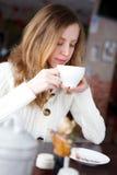 Café de consumición o té de la muchacha elegante hermosa joven Fotos de archivo