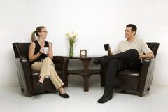 Café de consumición que se sienta del hombre y de la mujer. Imágenes de archivo libres de regalías
