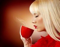 Café de consumición rubio hermoso de la mujer joven Fotos de archivo libres de regalías