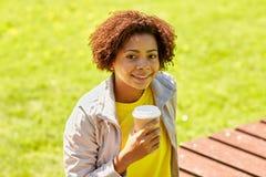 Café de consumición sonriente de la mujer africana al aire libre Imágenes de archivo libres de regalías