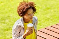 Café de consumición sonriente de la mujer africana al aire libre Imagenes de archivo