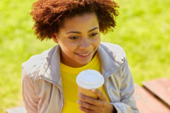 Café de consumición sonriente de la mujer africana al aire libre Fotografía de archivo