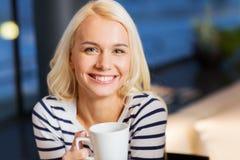 Café de consumición sonriente de la mujer joven en el café Imágenes de archivo libres de regalías