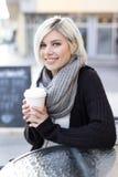 Café de consumición sonriente de la mujer rubia al aire libre en el café Foto de archivo libre de regalías