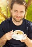 Café de consumición sonriente feliz del hombre en el jardín Fotos de archivo
