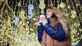 Café de consumición sonriente de la mujer europea de la taza de papel en el fondo amarillo de la Navidad de la luz del bokeh metrajes