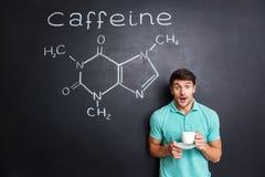 Café de consumición sorprendido del estudiante sobre la estructura exhausta de la molécula del cafeína imagen de archivo