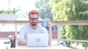 Café de consumición, trabajando en línea en el ordenador portátil, sentándose en el balcón al aire libre metrajes