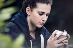 Café de consumición triste de la mujer joven del adolescente afuera Fotografía de archivo libre de regalías