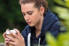 Café de consumición triste de la mujer joven del adolescente afuera Fotografía de archivo