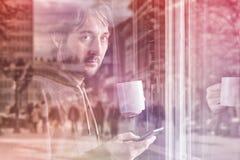 Café de consumición y el mandar un SMS con el teléfono móvil por mañana Imagenes de archivo