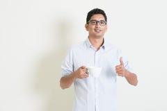 Café de consumición y pulgar del varón indio casual del negocio para arriba Foto de archivo