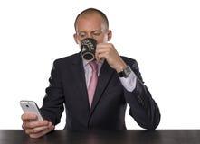 Café de consumición y que manda un SMS del hombre de negocios aislado en el fondo blanco Fotos de archivo libres de regalías