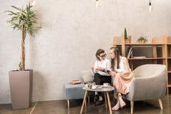 Café de couples lesbiens et d'utilisation smartphone potables ensemble Images libres de droits