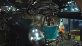 Café de derramamento da máquina do café dentro ao copo de papel azul filme