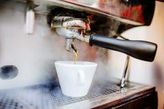 café de derramamento da máquina de café em uns copos, em um cappuccino e em um café Imagens de Stock