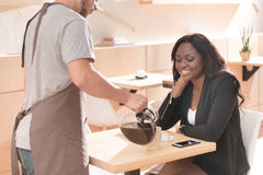 Café de derramamento do garçom para a mulher bonita que senta-se no café fotografia de stock