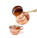 Café de derramamento em um copo Imagem de Stock