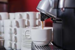 Café de derramamento em um copo de uma máquina do café foto de stock