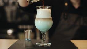 Café de derramamento em um vidro com espuma do leite filme