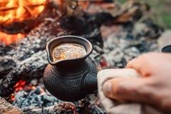 Café de ebulição no cezva turco em carvões da fogueira Campin luxuoso imagens de stock