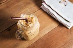 Café de gelo com leite e jornal na tabela foto de stock