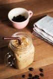 Café de gelo com leite e jornal na tabela imagem de stock