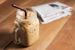 Café de gelo com leite e jornal na tabela imagens de stock