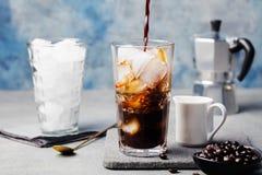 Café de gelo em um vidro alto e em feijões de café Imagem de Stock Royalty Free
