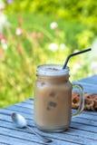 Café de gelo na caneca de vidro com leite e canela na tabela de madeira no jardim imagem de stock royalty free