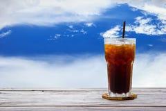 Café de glace, americano, thé de citron, kola sur la table en bois avec le ciel bleu et fond de nature de nuages Copiez l'espace Photographie stock