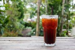 Café de glace, americano, thé de citron, kola sur la table en bois avec le fond vert de nature Copiez l'espace Photo libre de droits