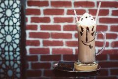 Café de glace crémeux sur la surface noire décorée du visage souriant photographie stock libre de droits